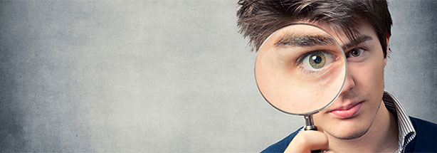 Young man looking through magnifying glass